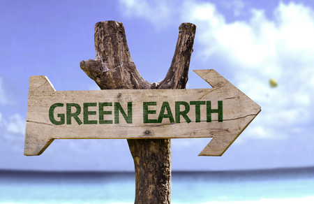 forestation: Green earth sign with arrow on beach background
