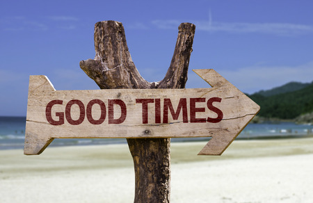 Good times sign with arrow on beach background