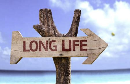Segno di lunga vita con la freccia su sfondo spiaggia Archivio Fotografico - 62034104