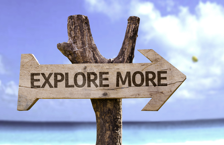 Explore more sign with arrow on beach background Stock Photo
