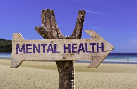 ビーチの背景にある矢印とメンタルヘルス記号 写真素材