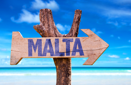 Malta sign with arrow on beach background Stock Photo
