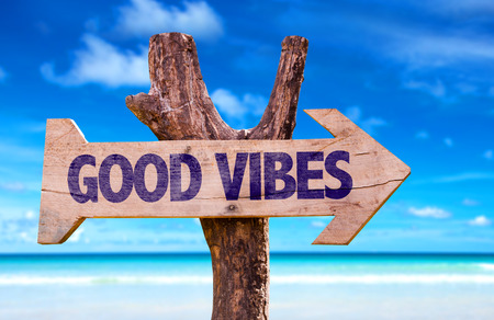 Good vibes sign with arrow on beach background