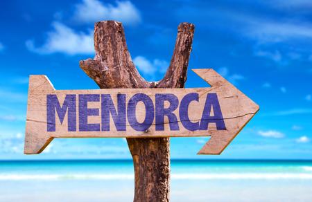 menorca: Menorca sign with arrow on beach background
