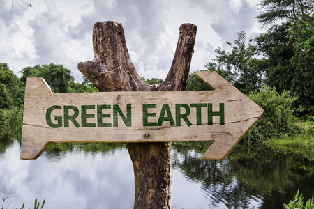 Wooden sign board in wetland with text: Green earth
