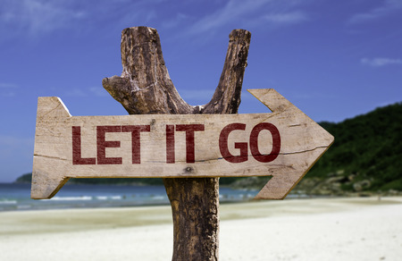 go sign: Let it go sign with arrow on beach background Stock Photo