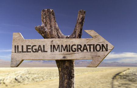Illegal immigration sign with arrow on desert background