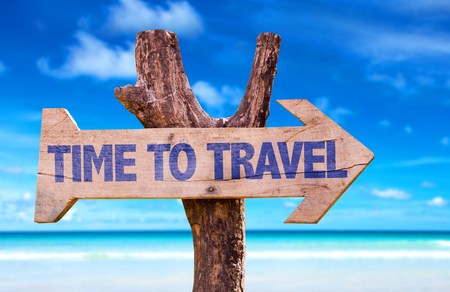 Time to travel sign with arrow on beach background Stock Photo