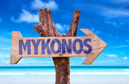 Mykonos sign with arrow on beach background