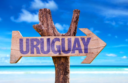 uruguay: Uruguay sign with arrow on beach background Stock Photo