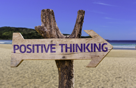 Positive thinking sign with arrow on beach background Stock Photo