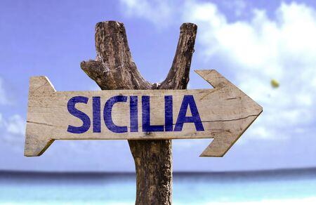 sicilia: Sicilia sign with arrow on beach background Stock Photo