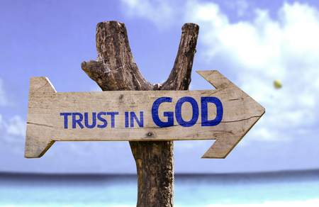 trust god: Trust in God sign with arrow on beach background