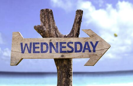 wednesday: Wednesday sign with arrow on beach background
