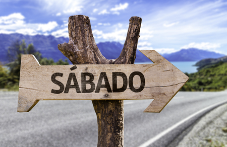 Sabado (Saturday in Spanish) sign with arrow on road background