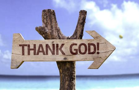 Thank God! sign with arrow on beach background Stock Photo