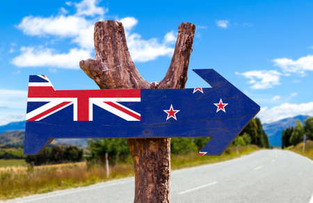 new zealand flag: New Zealand flag sign with arrow on road background Stock Photo