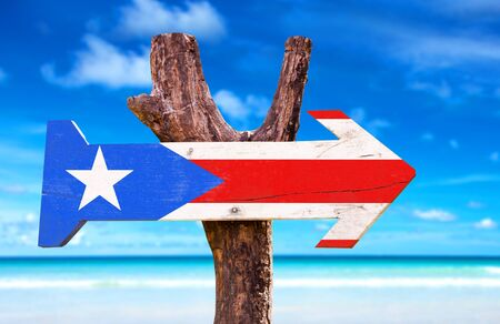 puerto rico: Puerto Rico flag sign with arrow on beach background Stock Photo