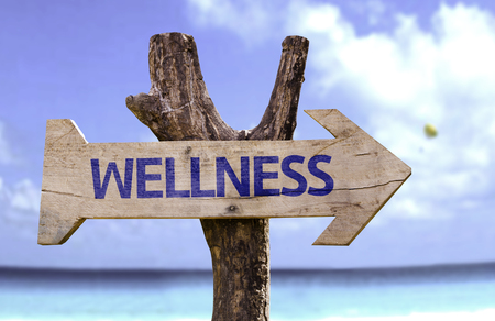 Wellness sign with arrow on beach background