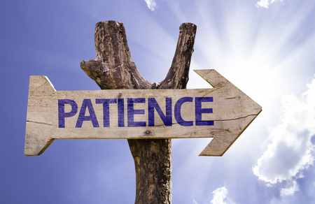 Patience sign with arrow on sunny background Stock Photo
