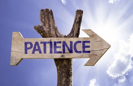 paciencia: signo de la paciencia con la flecha en el fondo de sol Foto de archivo