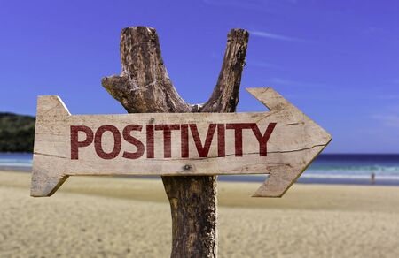 positivismo: Positivity sign with arrow on beach background