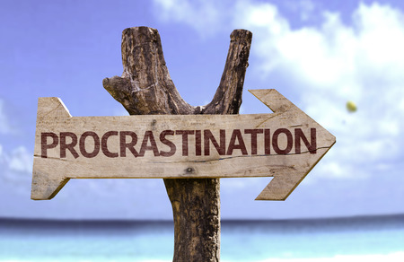 procrastination: Procrastination sign with arrow on beach background