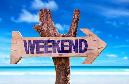 Weekend sign with arrow on beach background Stock Photo
