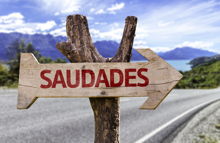 Saudades (miss you in Portuguese) sign with arrow on road background