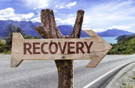 road to recovery: Recovery sign with arrow on road background Stock Photo