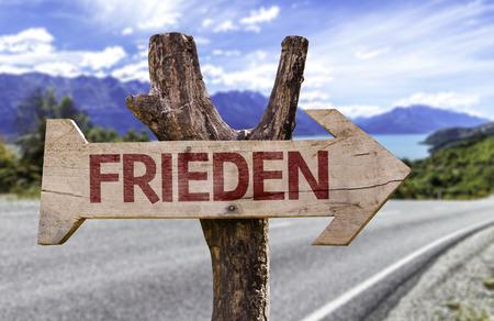 Frieden (paz en alemán) firmar con la flecha en el fondo de carreteras Foto de archivo - 62307947