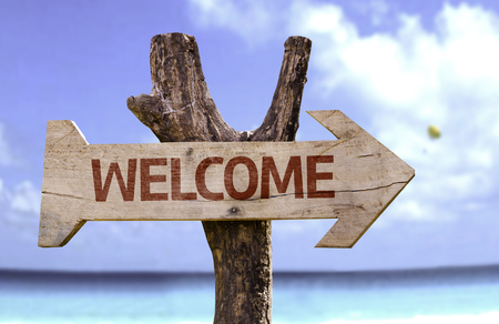 Welcome sign with arrow on beach background Stock Photo