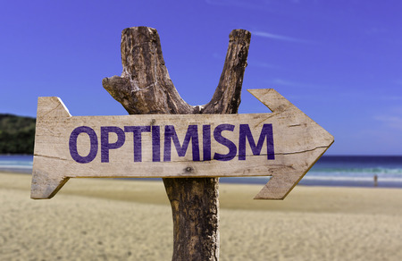 positivism: Optimism sign with arrow on beach background Stock Photo