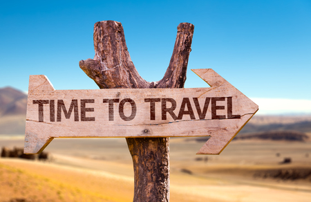 Time to travel sign with arrow on desert background Stock Photo