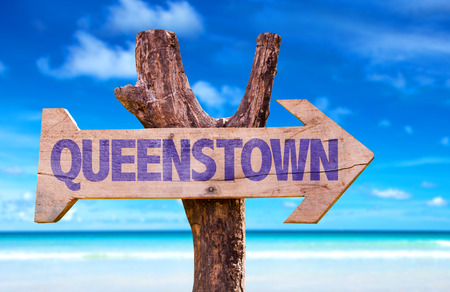 Queenstown sign with arrow on beach background