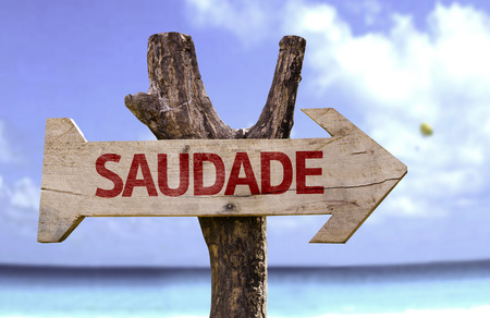Saudade (miss in Portuguese) sign with arrow on beach background