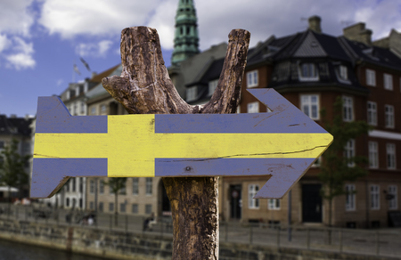 Sweden flag sign with arrow on city background