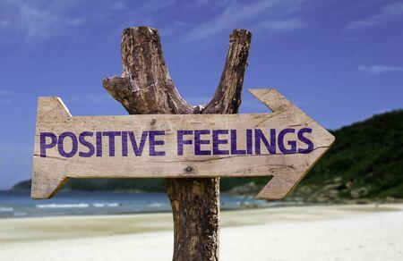positivism: Positive feelings sign with arrow on beach background