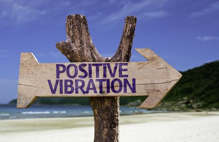vibration: Positive vibration sign with arrow on beach background