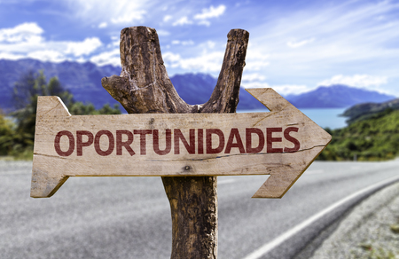 leadership potential: Oportunidades (opportunities in Portuguese) sign with arrow on road background Stock Photo