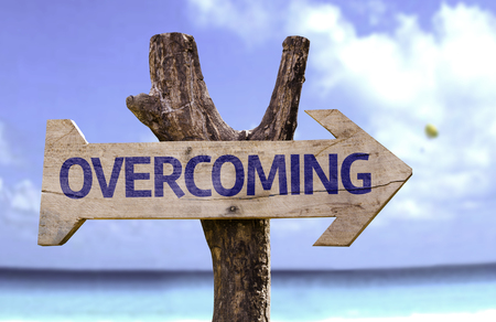 overcoming: Overcoming sign with arrow on beach background