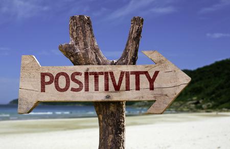 positivismo: signo de positividad con la flecha en el fondo de playa