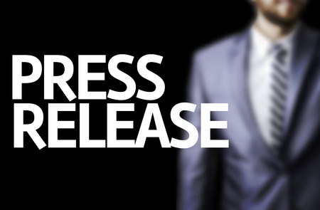 Business man in black background with the text: Press release Stock Photo