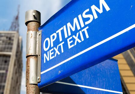 optimism: Optimism next exit signpost on building background Stock Photo