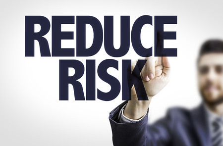 reduce risk: Business man pointing to transparent board with text: Reduce risk