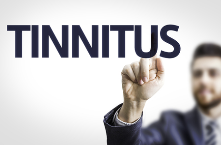 loudness: Business man pointing to transparent board with text: Tinnitus