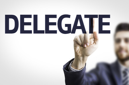 delegar: Business man pointing to transparent board with text: Delegate