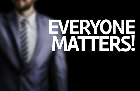 everyone: Business man in black background with the text: Everyone matters! Stock Photo