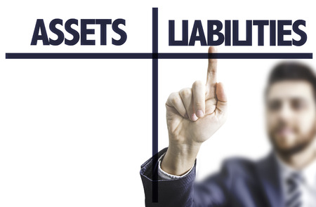 liabilities: Business man pointing to transparent board with text: Assets and liabilities Stock Photo