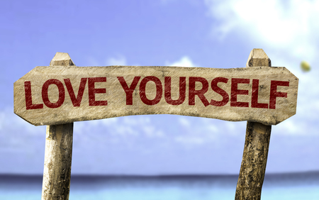 sign in: Wooden sign board in beach with text: Love Yourself Stock Photo